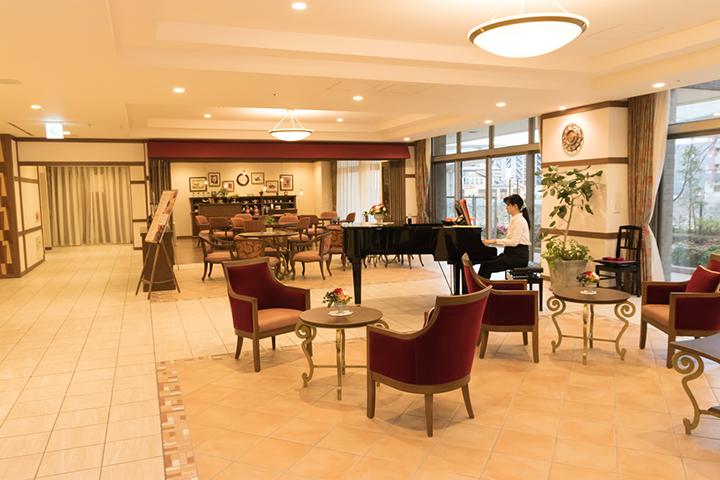 オリックス・リビング運営、グッドタイム リビング センター南のエントランスでのピアノの生演奏。入居者の憩いのスペースが充実している